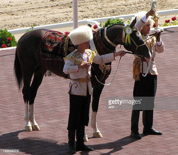 Turkmenistan's jockeys hold a horse called Khan of the Eagles during the Day of the Turkmen Race Horse holiday in Ashgabad on April 29 2012 President...