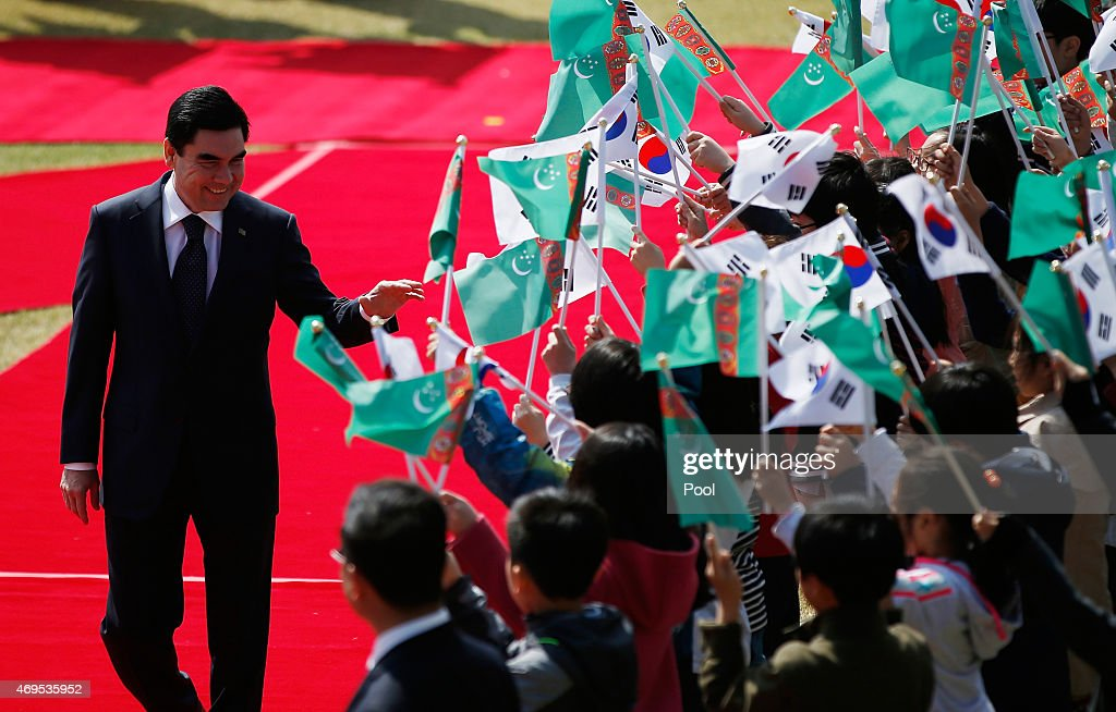 Turkmenistan's President Gurbanguly Berdimuhamedov greets children waving the national flags of two countries during a welcome ceremony at the Presidential Blue House on April 13, 2015 in Seoul, South Korea. South Korea. Turkmenistan and South Korea met to discuss economic exchanges and to strengthen bilateral relationships in trade, culture and diplomacy.