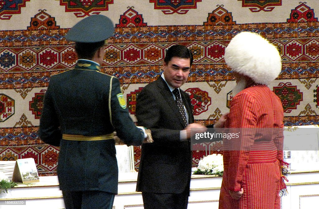 Turkmenistan's president Gurbanguly Berdymukhamedov (C) hands over an award to an unidentified man during a meeting of Turkmen elders in the city of Dashoguz, about 480 km northeast of the capital Ashgabat, on October 23, 2013.