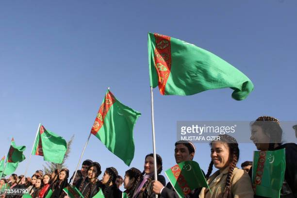 Turkmens hold Turkmenistan flags as they attend a newlyelected President Gurbanguly Berdymukhammedov's oath ceremony 14 February 2007 in Ashgabat...