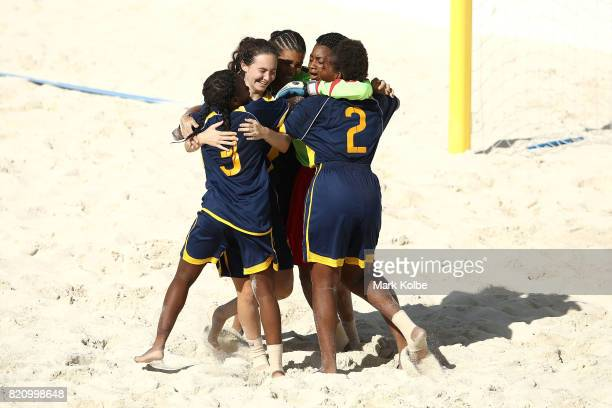 Turks Caicos Island celebrate victory during the girl's beach soccer bronze medal final match between the Bahamas and Turks Caicos Islands on day 5...