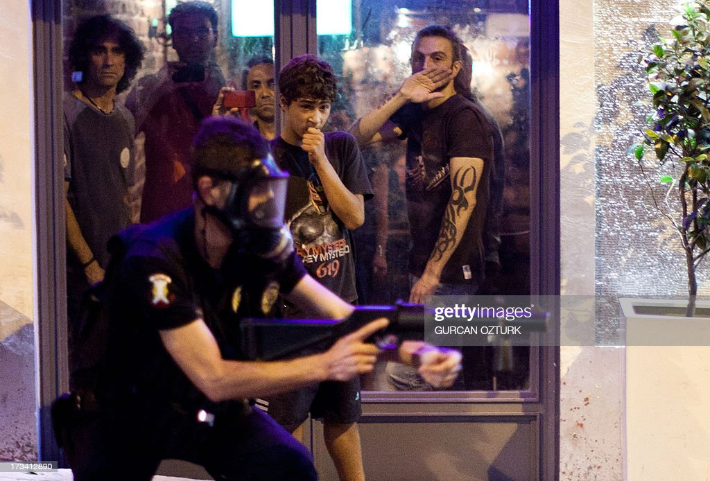Turksih people watch a riot policeman as he targets protestors on July 14, 2013 on Istiklal Avenue in the center of Istanbul. Turkish riot police fired rubber bullets, tear gas and water cannon to disperse hundreds of protesters trying to enter an Istanbul square that was the cradle of deadly unrest that engulfed the country in June. The police moved in when demonstrators protesting in the city's Beyoglu neighborhood against Prime Minister Recep Tayyip Erdogan moved toward nearby Taksim Square.