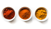 Turmeric, cayenne, and paprika spice powders in white bowls on a white background