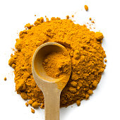 Pile of turmeric on white background with wooden measuring spoon
