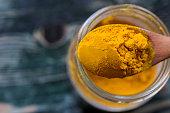 Turmeric powder in a wooden spoon