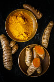 turmeric root and powder on black background
