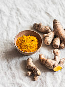 Turmeric root and turmeric powder on a light background