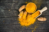 Fresh turmeric roots and turmeric powder on wood background