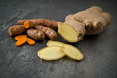 turmeric slices and ginger root sliced on gray background