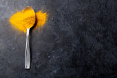 Turmeric spice in spoon over dark stone table background. Top view with copy space