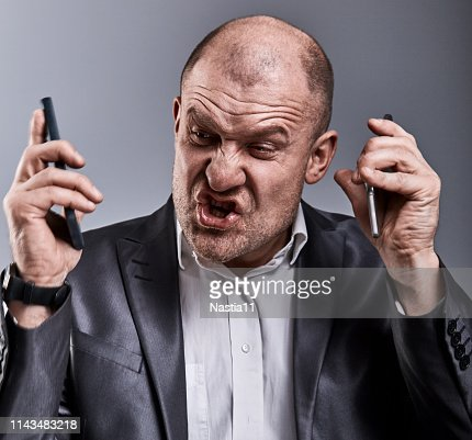 Turn nasty loud crying angry business man talking on two mobile phone very emotional in office suit on grey background. Closeup : Stock Photo