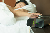 Young woman reach out one's hand Press the button to turn off the digital alarm clock in morning.