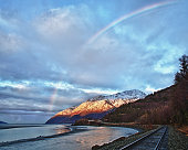 Train tracks, snow covered mountains and the Seward Highway are illuminated by the sunrise and a rainbow over Turnagain Arm in south central Alaska.