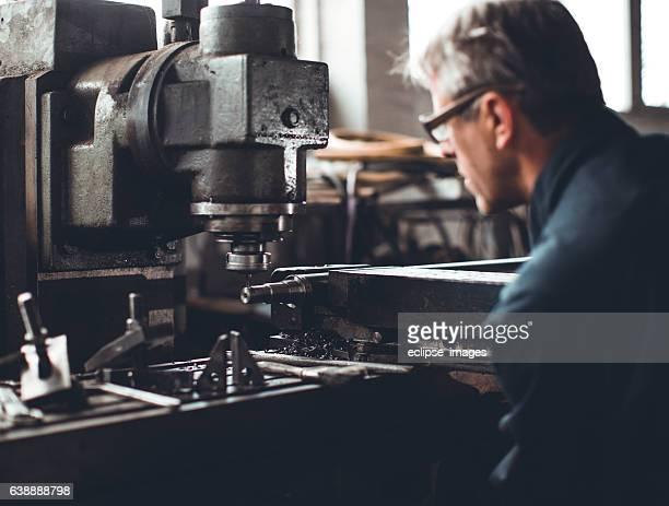 Turner worker working on drill bit in a workshop