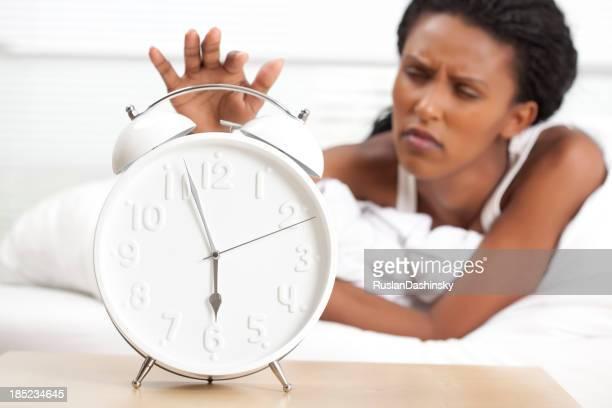 Turning off alarm clock.
