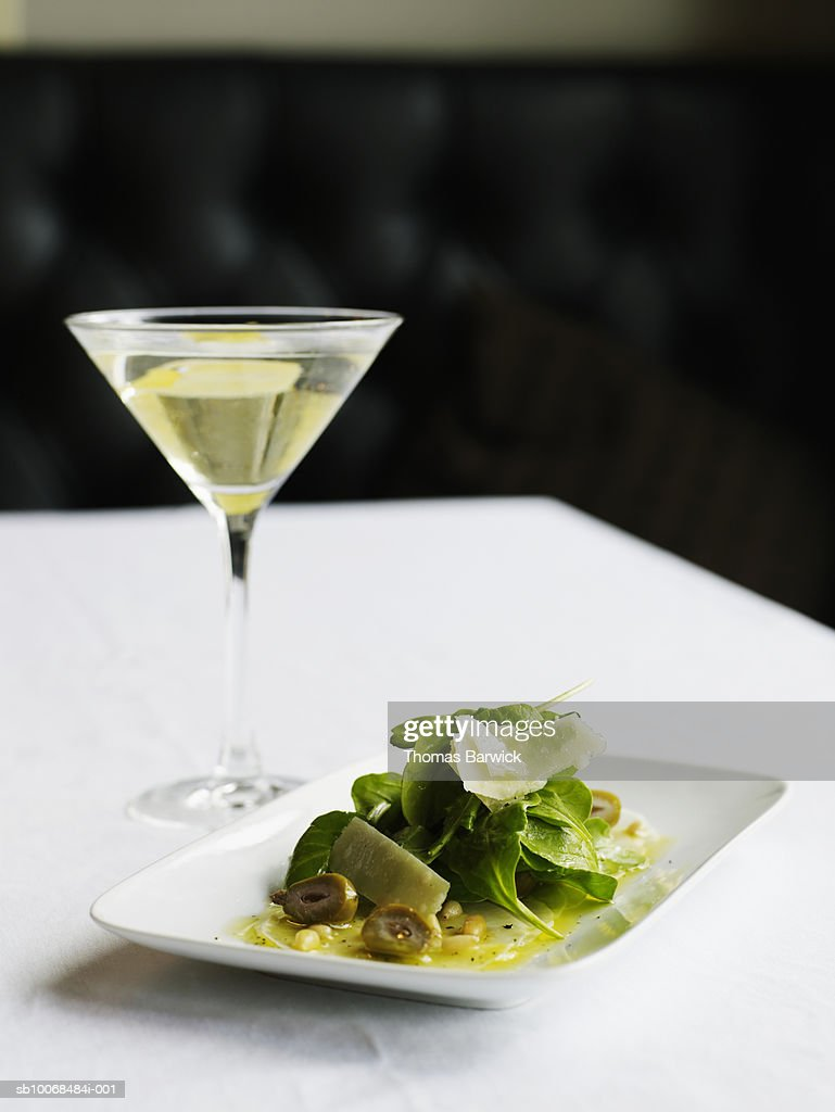 Turnip 'carpaccio' with arugula, parmesan, pine nuts and peaches, with vesper cocktail : Stock Photo