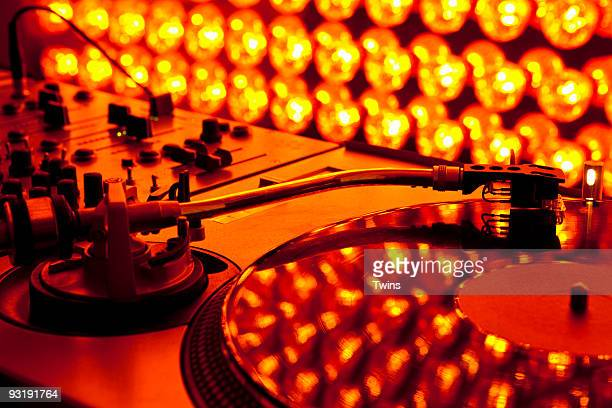 A turntable and sound mixer illuminated by lighting equipment