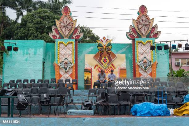 Turquoise blue carnival stage with colorful patterns and black plastic chairs lying haphazardly on its stairs