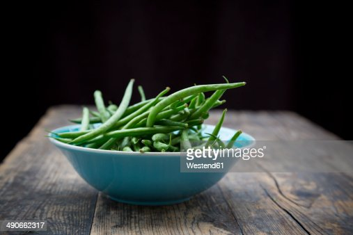 Turquoise bowl of green beans on wooden table