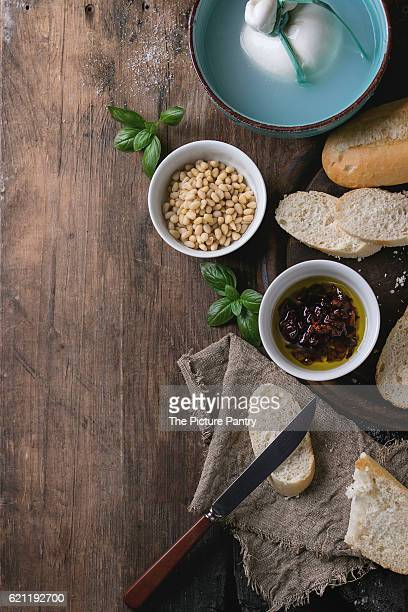 Turquoise bowl whole tied Italian cheese burrata in brine served with pine nuts, sliced bread, basil and dried tomatoes in olive oil with rag and knife over old wood background. Overhead view, space