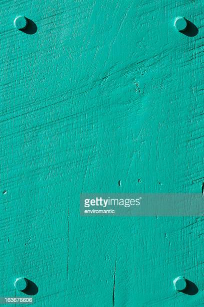 Turquoise grunge wood background with four bolts.