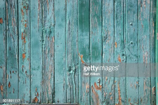 Turquoise painted weathered wooden fence with peeling - How to paint a wood fence ...