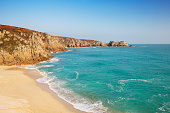 A beautiful beach with turquoise water at Porthcurno in Cornwall, England.