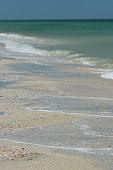 Bright sand with small surf and light-colored sea water with suspended sediment near the sore, leading to deep, dark water further out. Photo taken at Caladesi & Honeymoon Island state parks in Clearw