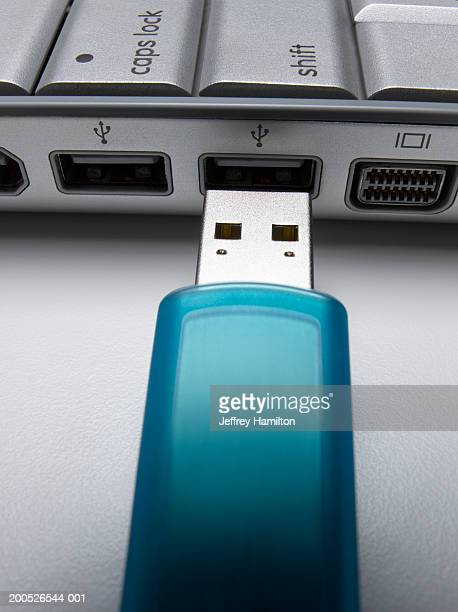 Turquoise USB flash drive about to connect to laptop, close-up