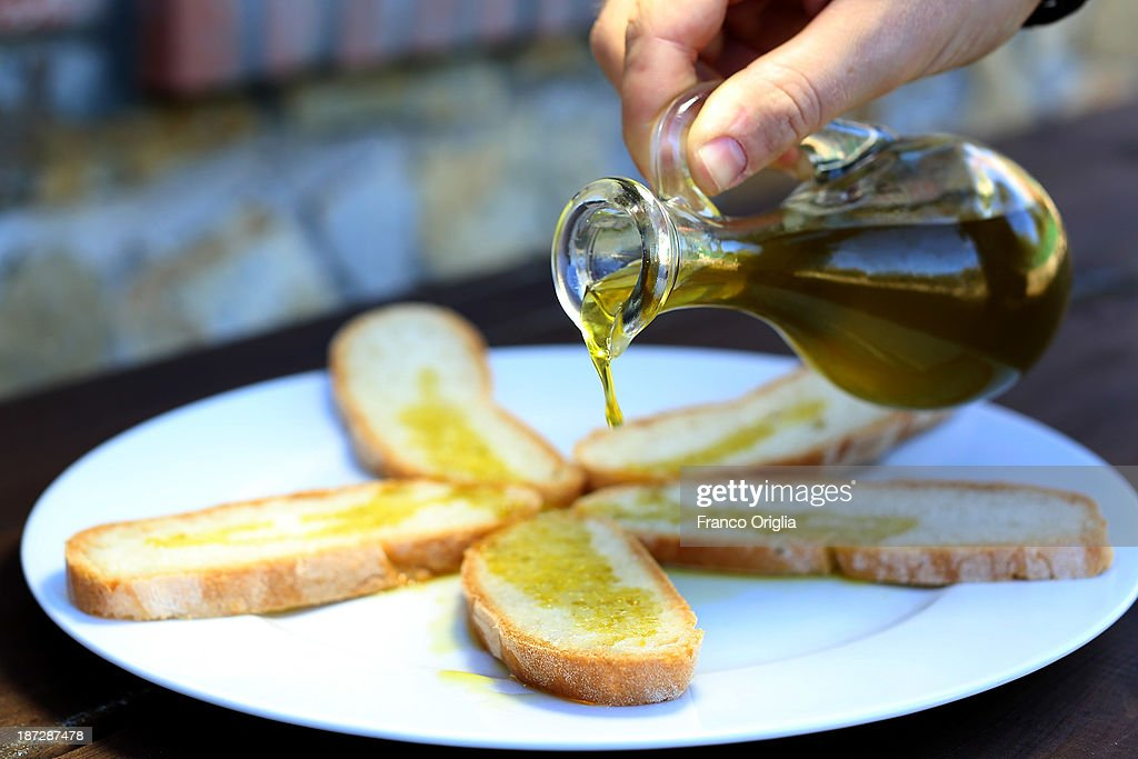 Tuscan bread is topped with fresh olive oil for a taste during the harvesting of olives at the Castello La Leccia estate on November 7, 2013 in Castellina in Chianti (Siena), Italy. An optimal climate, fertile land and skilled hands make Tuscan extra virgin olive oil one of the most popular food product in and outside of Italy.