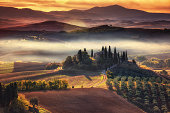 Tuscany, panoramic landscape with famous farmhouse rolling hills and valleys in beautiful golden morning light at sunrise in autumn, Val d'Orcia, Italy