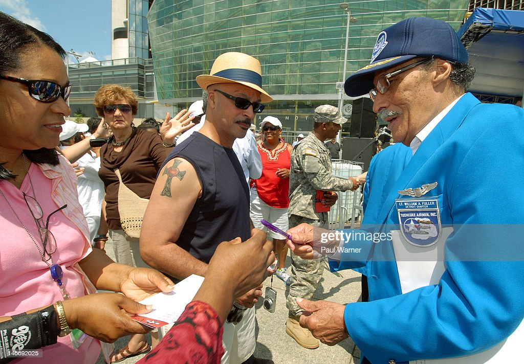 Tuskegee Airman William Fuller (R) signs autographs after the opening ceremony and salute to the Airmen at the 2012 Detroit River Days Festival at the Detroit RiverWalk on June 22, 2012 in Detroit, Michigan.