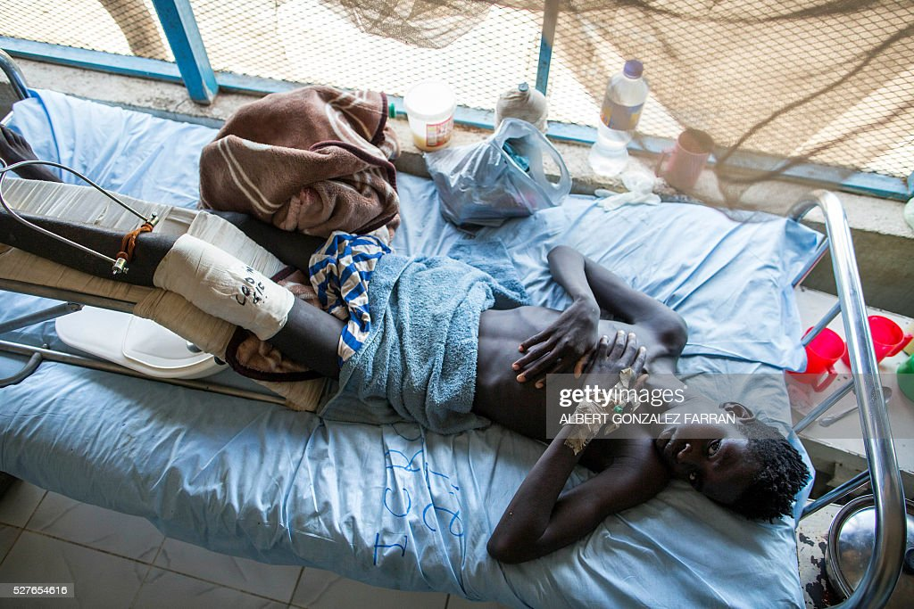 Tut Dan, 16, nurses his wounds at an ICRC-supported hospital in Maiwut in the Upper Nile region, about 20 kilometres from Gambella in Ethiopia, on May 3, 2016. Tut Dan was shot in the leg during an attack in Gambella and has been doing physical therapy to recover mobility. More than three dozen victims of violence have sought assistance at an International Committee of the Red Cross (ICRC)-supported hospital in Maiwut. The health facility is now providing medical and surgical care to the wounded of recent attacks near Gambella in Ethiopia where nearly 200 people were killed and more than 100 children abducted. Many of the 39 men, women and children admitted to the hospital are suffering from gunshot wounds as a result of the mid-April clashes along the Ethiopian border. The hospital is the only medical facility in the region providing surgical and advanced health care to the nearly 80,000 people living there. / AFP / Albert Gonzalez Farran