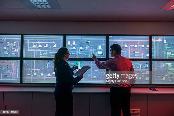 Tutor and student in front of monitors in ship's engine room simulator