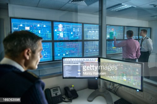 Tutor at computer monitors watching students in ship's engine room simulator