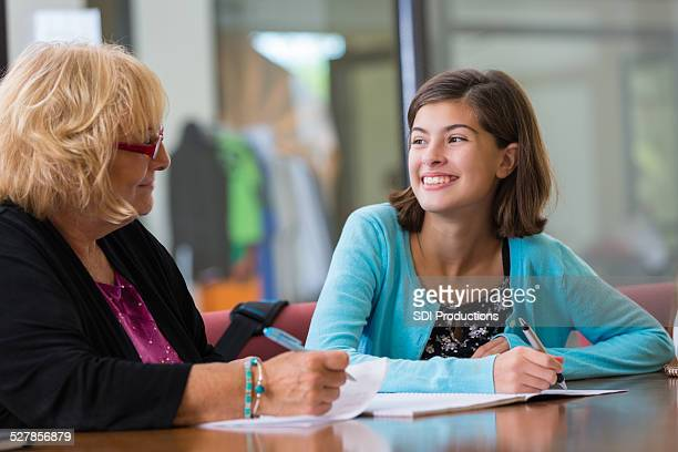 Tutor explaining homework assignment to preteen student