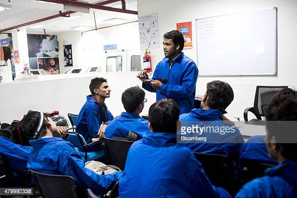 A tutor talks to students attending a welding theory class during vocational training at the Infrastructure Leasing Financial Services Institute of...