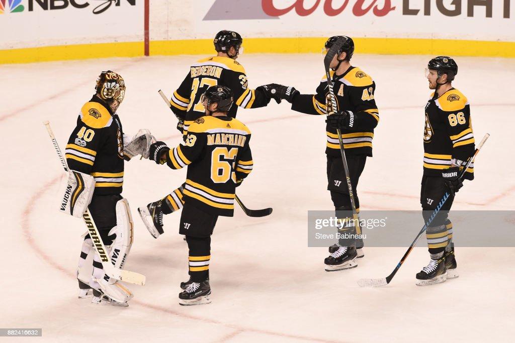 Tuukka Rask #40, Brad Marchand #63, Patrice Bergeron #37, David Backes #42 and Kevan Miller #86 of the Boston Bruins celebrate a win against the Tampa Bay Lightning at the TD Garden on November 29, 2017 in Boston, Massachusetts.