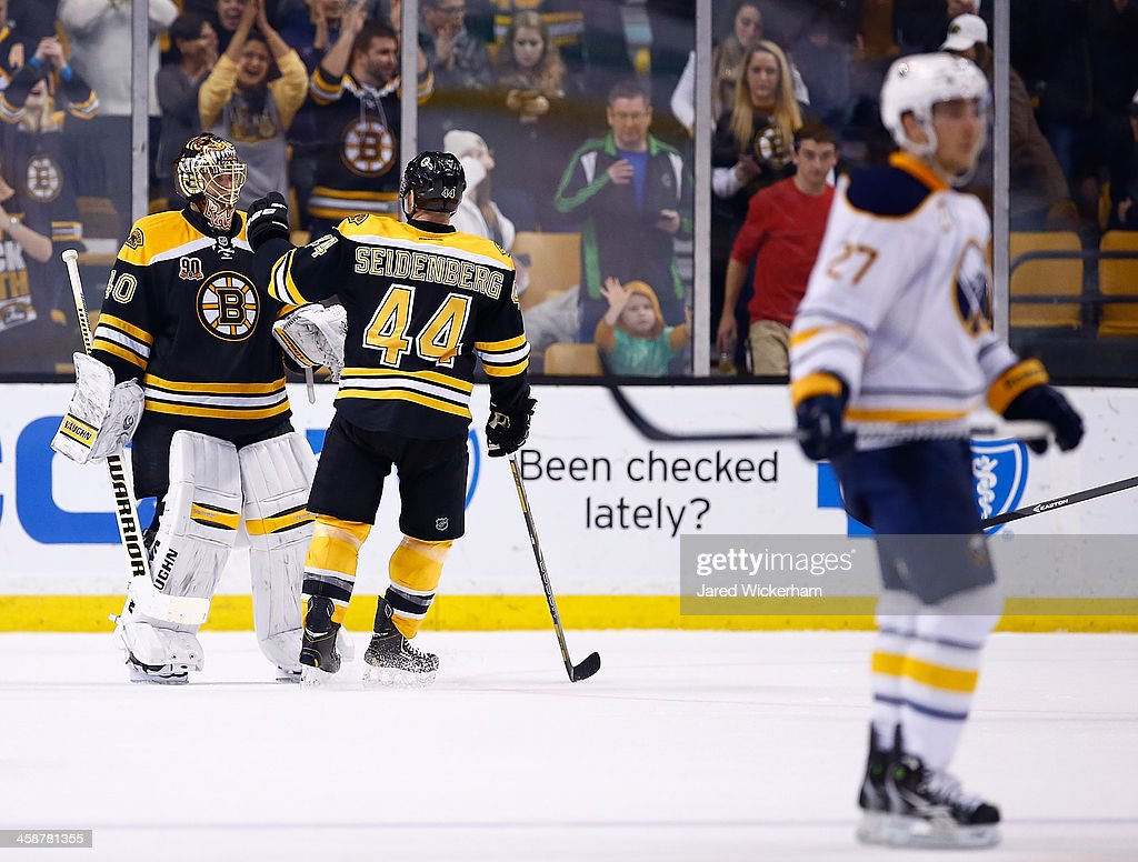 <a gi-track='captionPersonalityLinkClicked' href=/galleries/search?phrase=Tuukka+Rask&family=editorial&specificpeople=716723 ng-click='$event.stopPropagation()'>Tuukka Rask</a> #40 is congratulated by teammate <a gi-track='captionPersonalityLinkClicked' href=/galleries/search?phrase=Dennis+Seidenberg&family=editorial&specificpeople=204616 ng-click='$event.stopPropagation()'>Dennis Seidenberg</a> #44 of the Boston Bruins following their 4-1 win against the Buffalo Sabres during the game at TD Garden on December 21, 2013 in Boston, Massachusetts.