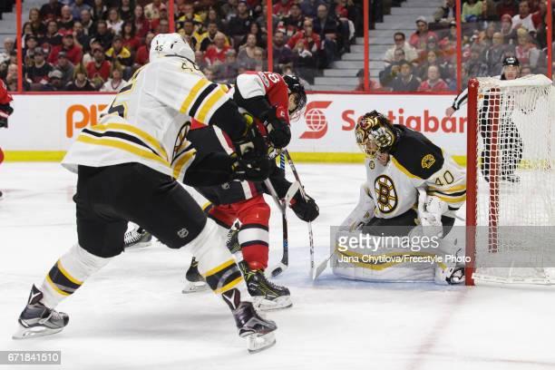 Tuukka Rask of the Boston Bruins makes a save against Ryan Dzingel of the Ottawa Senators as Joe Morrow of the Boston Bruins defends the net in...