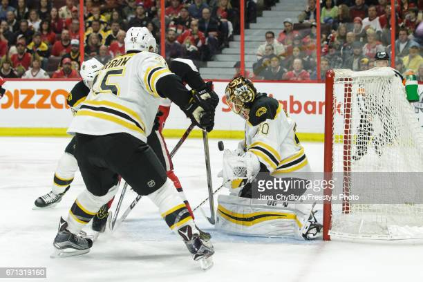 Tuukka Rask of the Boston Bruins makes a save against the Ottawa Senators as teammate Joe Morrow looks on in the 1st overtime period in Game Five of...