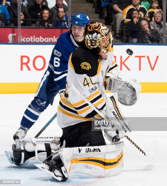 Tuukka Rask of the Boston Bruins makes a save as Mitch Marner of the Toronto Maple Leafs waits for a rebound during the first period at the Air...