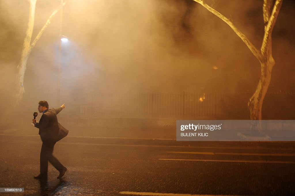A tv journalist reports as Istanbul fireteams try to control flames during a fire at Galatasaray University on January 22, 2013, in Istanbul. AFP PHOTO/BULENT KILIC