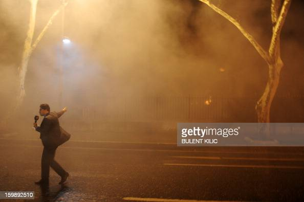 A tv journalist reports as Istanbul fireteams try to control flames during a fire at Galatasaray University on January 22 in Istanbul AFP...