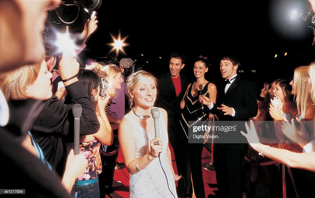 Tv Presenter, Actors and a Group of Fans at a Movie Premiere
