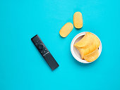 Tv remote, potato chips in a plate on bue background. Watching TV, top view