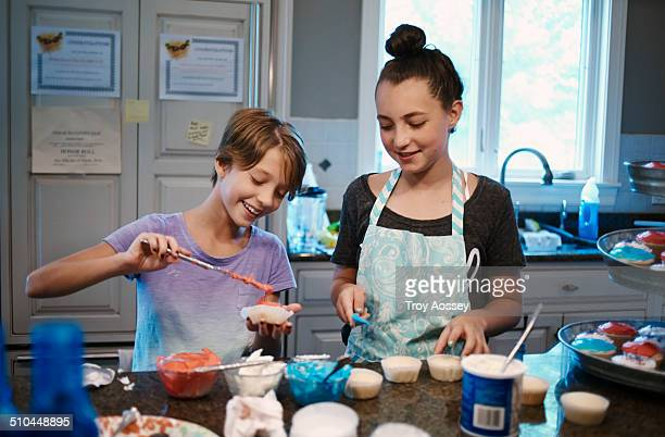 Tw girls making cupcakes at home in kitchen.
