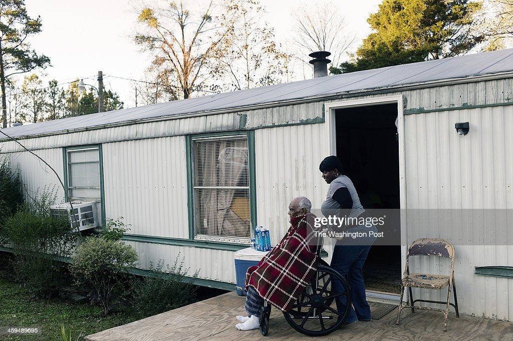 Twanda Blount, 39, helps her grandfather Chocolate Blount maneuver his wheelchair outside their trailer home. Chocolate Blount, who is 91, was discharged from hospice care after years of assistance and improving health. He was recently enrolled again in hospice and receives home visits weekly.