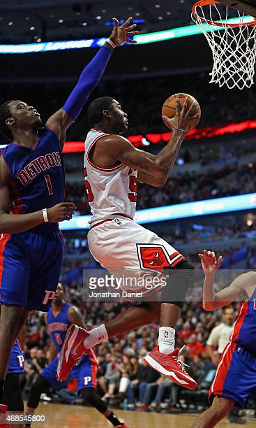 Twaun Moore of the Chicago Bulls leaps to pass under pressure from Reggie Jackson of the Detroit Pistons at the United Center on April 3 2015 in...