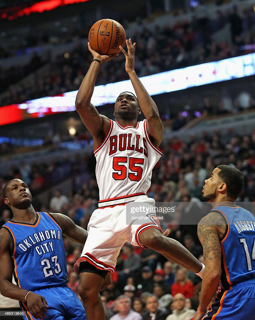 E'Twaun Moore #55 of the Chicago Bulls puts up a shot between Dion Waiters #23 and D.J. Augustin #14 of the Oklahoma City Thunder at the United Center on March 5, 2015 in Chicago, Illinois. The Bulls defeated the Thunder 108-105.